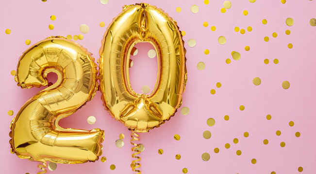 20 air balloon numbers on pink background. 20 k gold foil balloons with confetti. Birthday party flat lay with copy space long web banner
