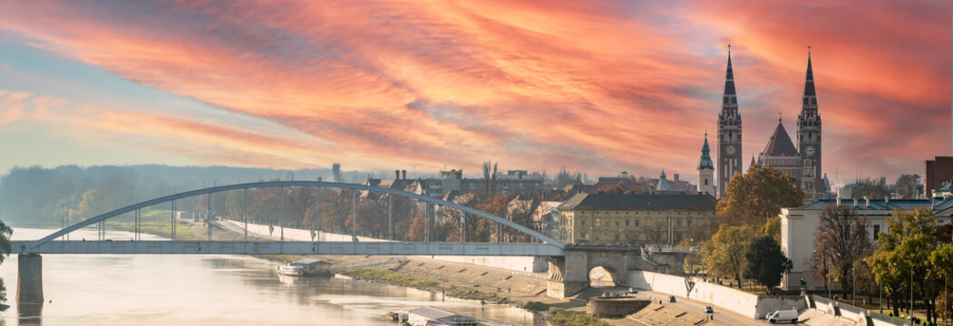 Panoramic View of Szeged Skyline Cityscape during golden hour sunset. Includes the river Tisa, Bridge and Votive Church of Szeged. Hungary