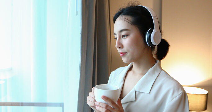 Asian women happy wearing headphones to music on their mobile phones and drinking coffee on relax time at home