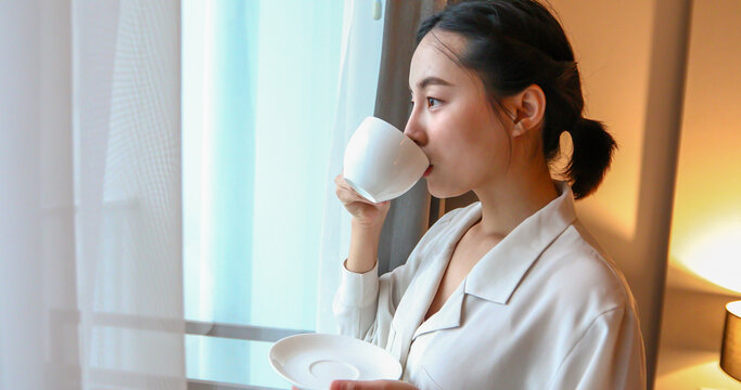 Asian woman drinking coffee and looking out of the window in the house.