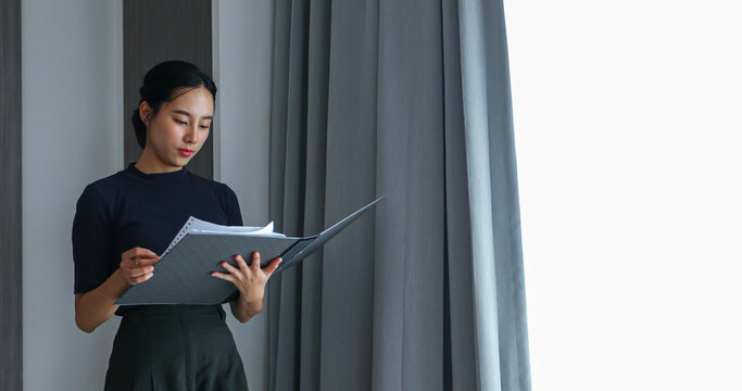Asian women holding files and reviewing documents for working at the office