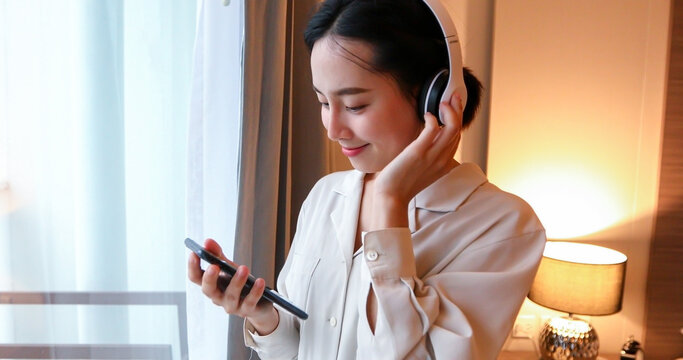 Asian women happy wearing headphones to music on their mobile phones on relax time at home