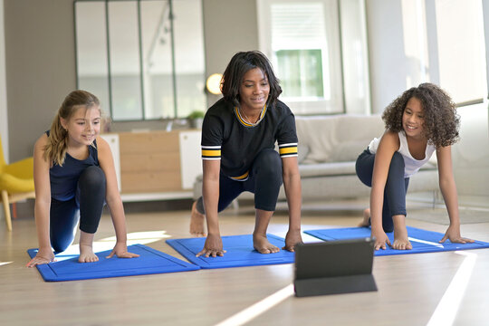 Young woman with kids doing fitness exercices at home, online class