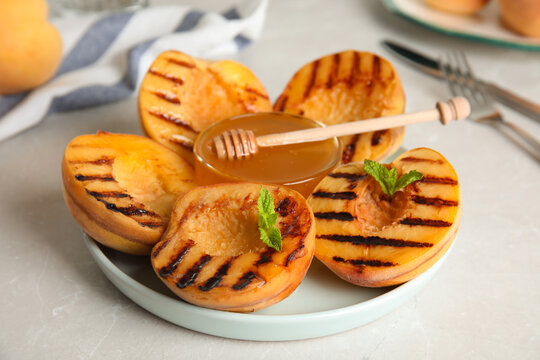 Delicious grilled peaches with honey and mint on grey  table