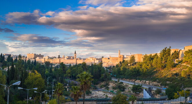 Franciscan Monastery of Saint Saviour, Jaffa Gate, Tower of David and the walls of Old City with a beautiful cloudy sky; panoramic view from the green Hinnom valley or Gehenna, Old City Jerusalem