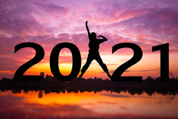 Silhouette  and New year sunset background. Woman standing and show hand. She is Jumping between 2020 and 2021 word.new year,success,2021,Photo Silhouette and new year.