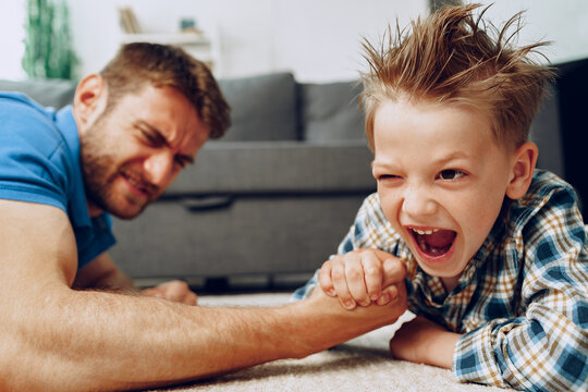 Father and son arm wrestling on carpet at home