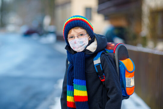 Little kid boy with glasses wearing medical mask on the way to school. Child backpack satchel. Schoolkid on winter day with warm clothes. Lockdown and quarantine time during corona pandemic disease