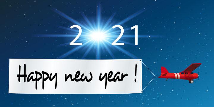 Carte de vœux 2021 montrant un avion rouge tirant une banderole blanche pour souhaiter la bonne année, devant un ciel étoilé.