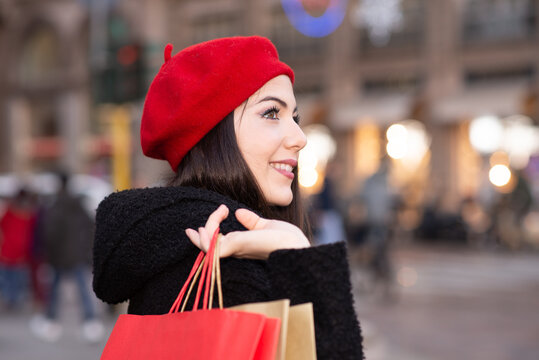 Young woman with shopping bags and Christmas gift