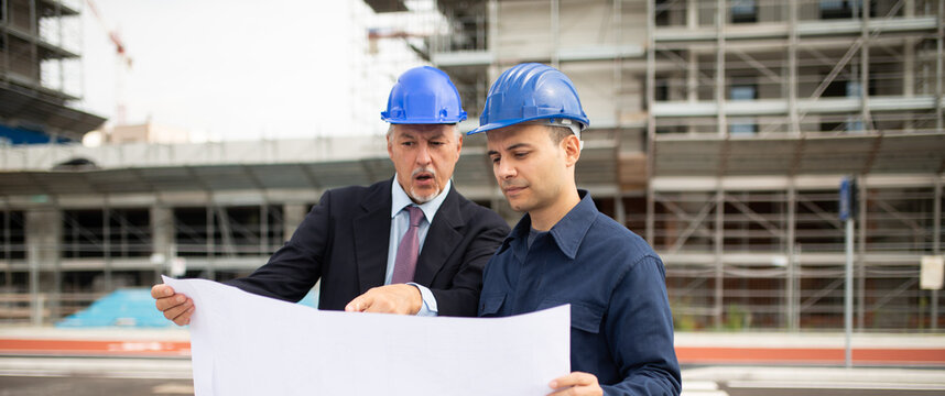 Architect and site manager discussing about a drawing