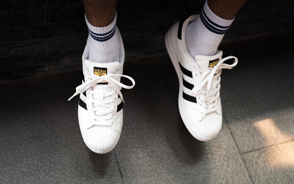 Closeup of white Adidas Superstar sneakers on man's feet on May 20, 2019 in Bangkok, Thailand.