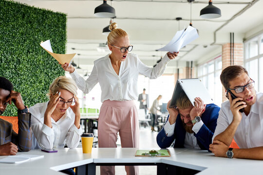 rude angry female boss executive is dissatisfied irritated by employees, scream at them, incompetent workers. in modern office
