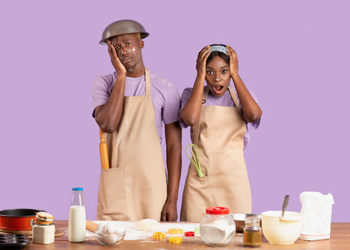 Baking disaster concept. Desperate young black couple having difficulty cooking over lilac background