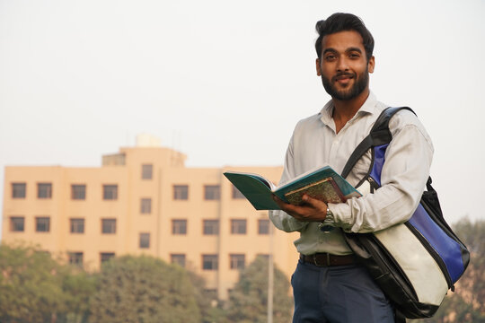 Indian Student with books and bag at college campus