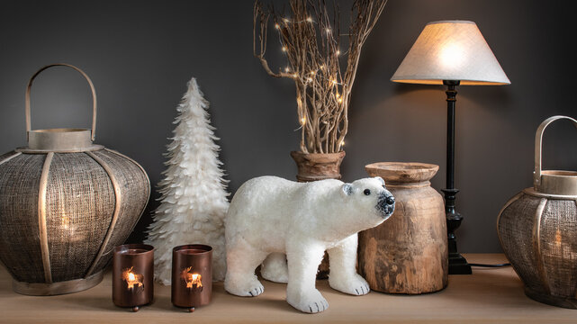 Winter country house decor.  Electric lamp, lanterns, candle holders with burning flame, Christmas feather tree, wooden pots and a decorative polar bear against a dark wall.