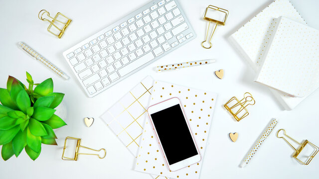 Stylish white and gold theme desktop workspace with keyboard, notebooks and smart phone. Top view blog hero header creative composition flat lay.