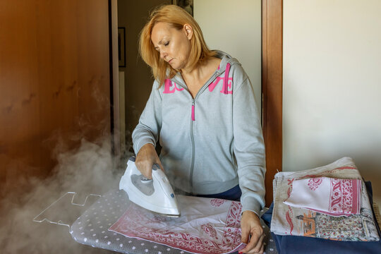 Middle-aged blonde woman with disgusted face ironing a pile of clothes with the ironing board wrapped in a large cloud of steam coming out of the iron