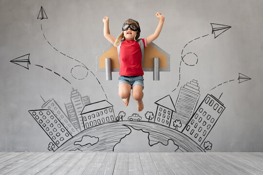 Child with jetpack jumping against grey concrete background