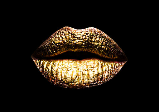 Gold lip. Closeup view of sexual beautiful female closed golden lips isolated on black background.