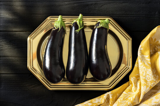 Eggplants on a golden plate with a vintage yellow napkin