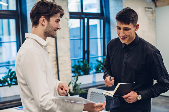 Businessman showing clipboard to colleague