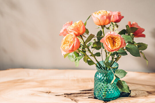 Rustic bouquet of roses in vase on table in sunlight