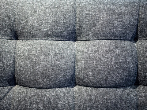 Gray textile texture of soft sofa with knobs
