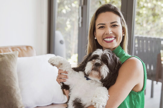 Portrait of beautiful Brazilian woman and her pet shih tzu dog looking at camera at home, making vedio call, recording vlog, women's day concept