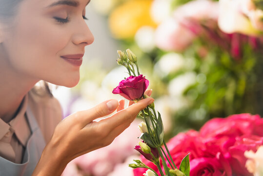 Happy female florist with closed eyes smelling eustoma flower with blurred flowers on background