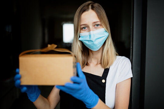 Cropped view of young waitress in latex gloves and protective face mask holding paper box package near window of cafe