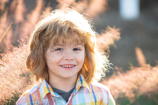 Cute child portrait. Happy boy child is smiling enjoying life. Portrait of young boy in nature, park or outdoors. Concept of happy family or successful parenting.