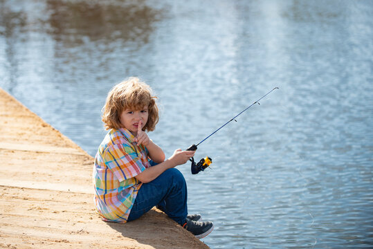 Serious, little boy child is fishing on the river with a fishing rod.