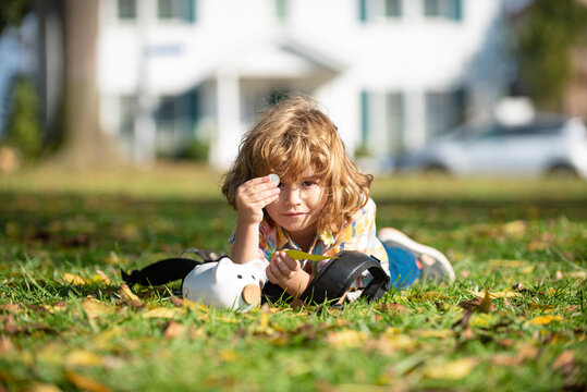 Outdoor portrait of a cute little boy holding money. Child saving with one coin. Portrait kid with piggy bank and coin. Getting started saving money,