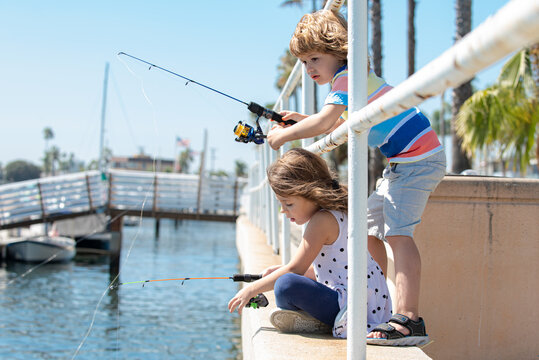 Two young cute children fishing in a sunny summer day. Kids are playing on sea. Friendship.