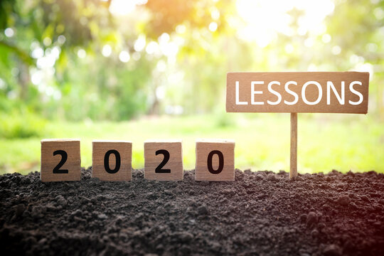 Life lessons and learnings from the year 2020 concept. A tree branch with a single remaining last leaf hanging beside a 2020 learning in wooden blocks at sunset.
