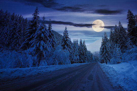 road through mountain landscape in winter at night. spruce forest covered in snow. dramatic sky with clouds glowing in full moon light