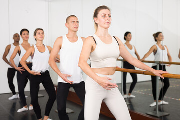 Group of multiethnic dancers standing with one hand on barre and reaching over hand .in bright...