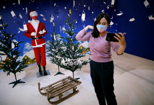 A woman tries to take selfie photos in front of a photo spot featuring Christmas season scene and masks at Tokyo Mask Land, amid the coronavirus disease (COVID-19) outbreak, in Yokohama
