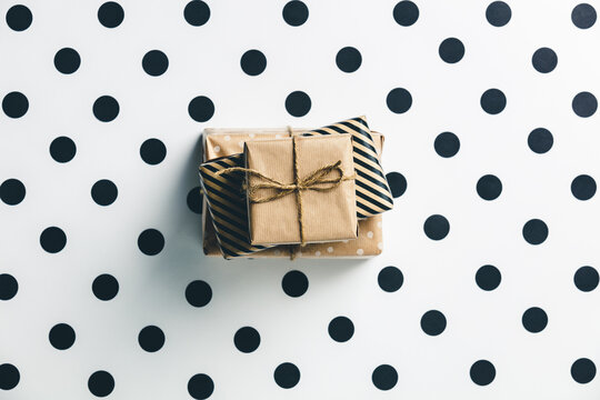 Eco style gift boxes on white polka dots background.