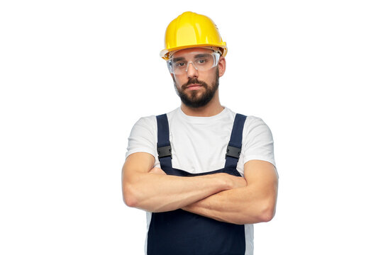 profession, construction and building - male worker or builder in yellow helmet and goggles with crossed arms over white background