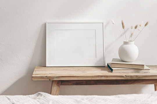 Winter still life. Horizontal white frame mockup on vintage wooden bench, table. Modern white ceramic vase with pine tree branches, Christmas paper ornaments and books. White wall background.