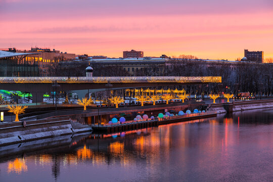 View of Zaryadye Park with soaring bridge, Moscow river with reflection in the water at dawn on new year and Christmas holidays. Moscow, Russia