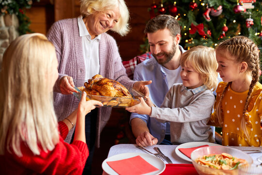 grandma bring chicken at table, contemporary large multi-generation family sitting by served festive table on Christmas day, going to celebrate
