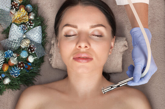 Beautician makes a procedure Microdermabrasion to beautiful woman. Next to her are Christmas decorations. New Year's and Cosmetology concept.
