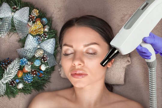 Carbon face peeling procedure in a beauty salon. Next to her are Christmas decorations. New Year's and Cosmetology concept.