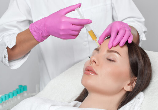 Cosmetologist does prp therapy on the face of a beautiful woman in a beauty salon. Cosmetology concept.