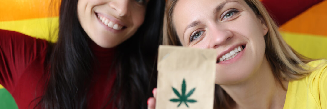 Two women are holding a lgbt flag and paper bag with marijuana sign. How marijuana affects sexual orientation concept