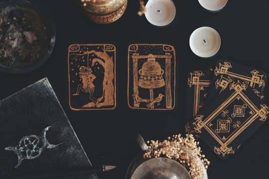 Flat lay of black and gold tarot card art. Hand made, not real diy vintage antique looking tarot cards on black table. Messy wiccan witch altar with grimoire, flowers, candles on it. The hanged man.