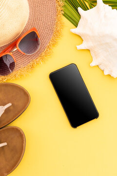 Sunglasses, flip flops, sunhat, shell and smartphone on yellow background